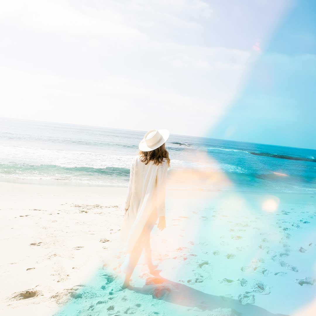 A photo of fine artist, Stefanie Bales at the beach in an all white outfit and hat.